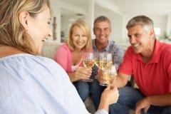 Sociala mitt- ålderpar som tillsammans hemma dricker Arkivbild