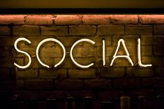 Sociale firmi dentro le luci gialle al neon Fotografia Stock Libera da Diritti