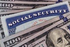 Socialförsäkringkort och en säng av pengar som föreställer den höga levnadskostnaden på en fast inkomst II royaltyfri foto
