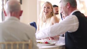 Socialising At A Dinner Party. People are socialising at a wedding dinner party while passing plates and enjoying food stock video footage