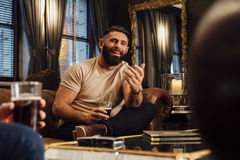 Socialising Over Drinks. Man is sitting in the lounge of a bar with some friends. He is talking to them with a pint of beer in his hand Stock Photos