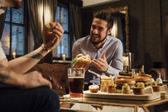 Socialising Over Food. Man is laughing and talking to his friend over a meal in a bar/restaurant. They are eating burgers and drinking beer Royalty Free Stock Photos
