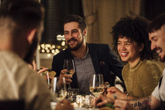 Socialising Over A Meal. Group of friends are enjoying a meal in a restaurant. They are are talking and laughing while eating and drinking wine Stock Photography