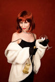 Socialite with brassy red hair and wine bottle Royalty Free Stock Photos