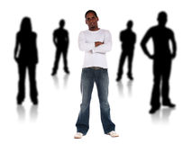 Socialize. An attractive young man standing among several black silhouettes. All isolated on white background Stock Photos
