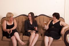 Socializing woman. Three well dressed and diverse woman socializing with wine Royalty Free Stock Images