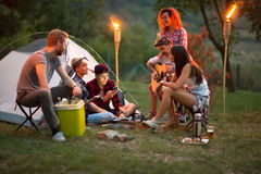Socializing youngsters in front of tent at night. Socializing youngsters in front of tent with beer, guitar and drums at night Royalty Free Stock Image