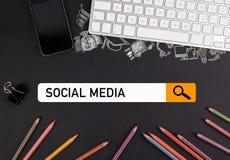 Socialt medelbegrepp färgrika blyertspennor och ett datortangentbord med en mobiltelefon på en svart tabell Arkivfoto