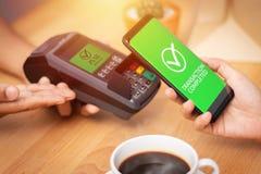 Sociedad Cashless, cuenta que paga del cliente con smartphone usando tecnología de NFC en el terminal de punto de venta en café d foto de archivo libre de regalías