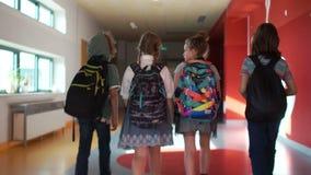 Società amichevole degli adolescenti nelle fretta giù il corridoio da classificare, retrovisione della scuola Due ragazze e due r archivi video