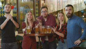 Società degli amici - giovani tipi e ragazze che tengono i vetri di birra, calcio di sorveglianza, ridenti e sorridenti alla barr archivi video