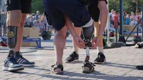Società della gente con le gambe prostetiche che stanno sulla strada asfaltata su fondo unfocused della folla video d archivio