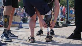 Società della gente con le gambe prostetiche che stanno sulla strada asfaltata su fondo unfocused della folla archivi video