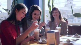 Società delle amiche allegre che bevono la bevanda del caffè e che ridono seduta alla tavola in caffè stock footage