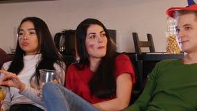 Società di giovani amici che spendono tempo che guarda insieme TV e che mangia popcorn e le patatine fritte archivi video