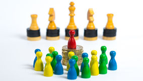 Society. Board game figures in front of white background - Concept of our society - Workers in the front, the wealthy business man on the pile of money and the Royalty Free Stock Photo