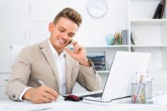 Socio comercial con el teléfono y el ordenador portátil elegantes imagen de archivo libre de regalías