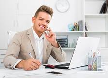 Socio comercial con el teléfono y el ordenador portátil elegantes foto de archivo