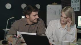 Socio commerciale che discute i rapporti finanziari davanti al computer portatile nell'ufficio di notte stock footage
