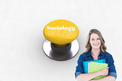 Sociology against yellow push button. The word sociology and smiling student holding notebook and file  against yellow push button Royalty Free Stock Photography