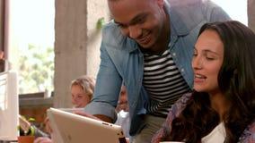 Socios comerciales casuales que trabajan junto en una tableta almacen de metraje de vídeo
