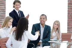 Socios comerciales de aplauso del equipo del negocio después de firmar el contrato foto de archivo