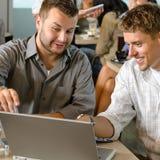 Socios comerciales de los hombres que trabajan en el café de la computadora portátil foto de archivo