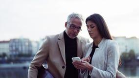 Socios comerciales del hombre y de la mujer con la situación del smartphone en la ciudad, tomando el selfie metrajes