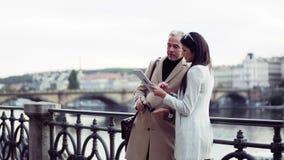 Socios comerciales del hombre y de la mujer con la tableta que hace una pausa un r?o en la ciudad de Praga metrajes