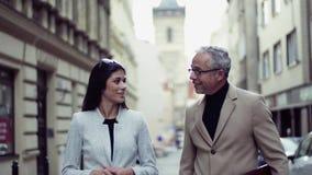 Socios comerciales del hombre y de la mujer que caminan al aire libre en la ciudad de Praga, hablando almacen de metraje de vídeo