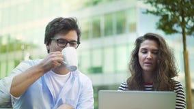 Socios comerciales jovenes que discuten su trabajo en café de consumición del café del verano almacen de metraje de vídeo