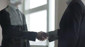 Socios comerciales que confirman trato con el apretón de manos firme, trabajo en equipo, sociedad almacen de metraje de vídeo