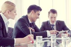 Socios comerciales que discuten documentos e ideas en la reunión Imagen de archivo