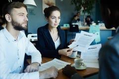 Socios comerciales que discuten trato en la mesa de reuniones foto de archivo