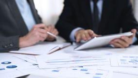 Socios comerciales que intercambian ideas sobre el desarrollo de mercado, usando la PC de la tableta imagenes de archivo