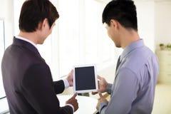 Socios comerciales que miran la tableta imágenes de archivo libres de regalías