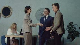 Socios comerciales que saludan en oficina antes de encontrar almacen de video
