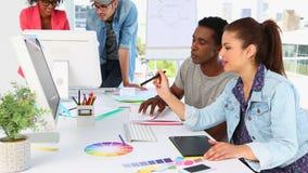 Socios creativos que trabajan junto feliz pareciendo la pantalla