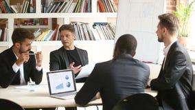 Socios masculinos multirraciales que discuten el documento de negocio en la reunión en la sala de reunión almacen de video