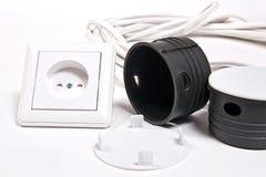 Sockel und Stromkabel auf weißer Oberfläche Lizenzfreies Stockbild