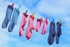 Socken auf einer Wäscheleine gegen blauen Himmel Lizenzfreies Stockbild
