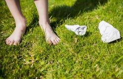 Socken auf grünem Gras mit menschlichen Füßen Stockfotos