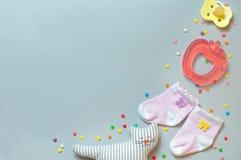 Socken-, soother-, teether- und Schlafenkatzenspielzeug über grauem backgroun Lizenzfreie Stockbilder