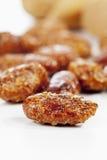 Socker grillade mandlar på vit bakgrund Royaltyfri Foto