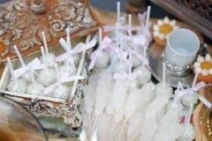 Socker på pinnar och rosa färgpopkakor Royaltyfri Bild