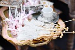 Socker på pinnar och rosa färgpopkakor Arkivfoton
