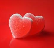 Sockerhjärtor på röd bakgrund royaltyfri bild