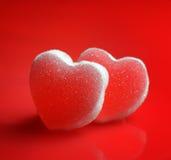 Sockerhjärtor på röd bakgrund Royaltyfri Foto