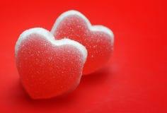 Sockerhjärtor på röd bakgrund arkivfoton