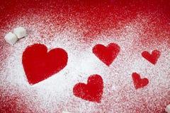 Sockerhjärtor på röd bakgrund Fotografering för Bildbyråer